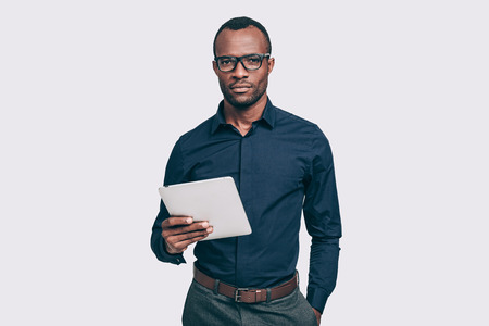african business man: Confident business expert. Handsome young African man holding digital tablet and looking at camera while standing against grey background