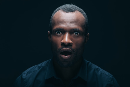 masculinity: No way! Portrait of surprised young African man looking at camera and keeping mouth open while being in front of black background