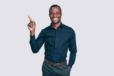 Look at this! Handsome young African man pointing up and smiling to you while standing against grey background Imagens