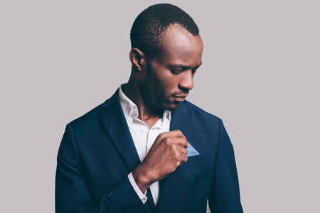 male fashion model: Everything should be perfect. Portrait of confident young African man adjusting his smart casual jacket while standing against grey background