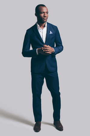 charisma: Confidence and charisma. Full length of handsome young African man in full suit holding hands clasped and looking away while standing against grey background Stock Photo