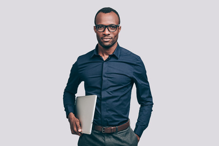 african business man: Confident business expert. Handsome young African man carrying laptop and looking at camera while standing against grey background Stock Photo