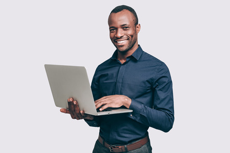 black male: How may I help you? Handsome young African man working on laptop and smiling to you while standing against grey background Stock Photo
