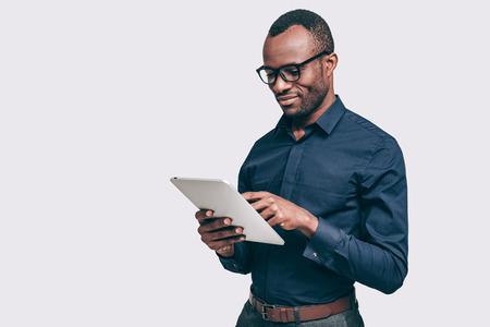仕事でビジネスの専門家。灰色の背景に対して立っている間デジタル タブレットに取り組んでいるハンサムな若いアフリカ男