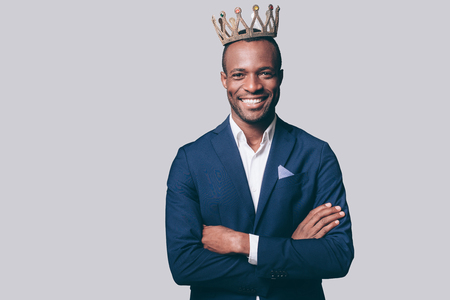 Like a king. Handsome young African man in crown and smart casual jacket looking at camera and smiling standing against grey background
