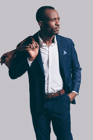 shoulder carrying: Stylish and handsome. Handsome young African man in full suit carrying brown leather bag on shoulder and looking away while standing against grey background