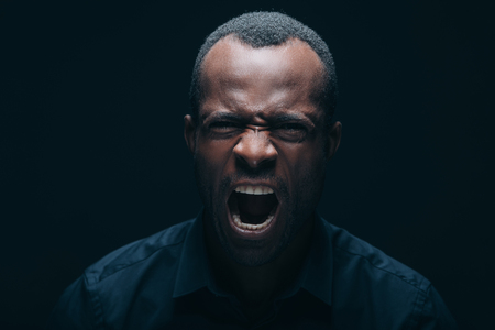 personne en colere: Feeling so angry! Portrait of furious young African man looking at camera and shouting while being in front of black background Banque d'images