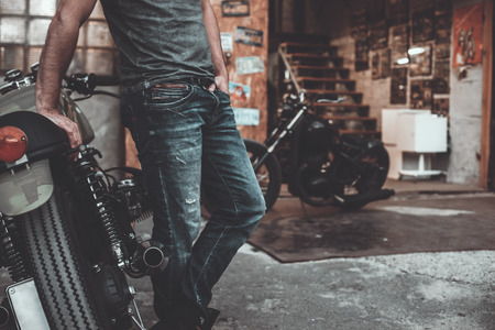motorcycle repair shop: Man near his bike. Confident young man keeping arms crossed and looking at camera while standing near his motorcycle garage or repair shop