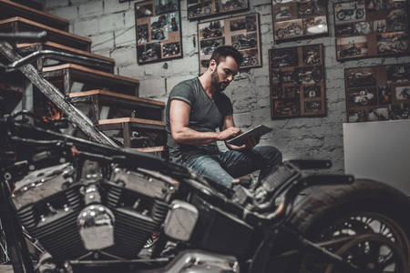 motorcycle repair shop: Planning his week. Confident young man holding digital tablet and looking at it while sitting near motorcycle in repair shop