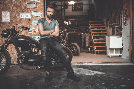 business services: Bike is my life. Handsome young man keeping arms crossed and looking at camera while leaning at his bike with repair shop in the background