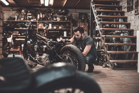 Mens die fiets herstelt. Zekere jonge mens die motorfiets in reparatiewerkplaats herstellen Stockfoto