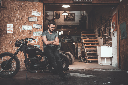 cool man: Man near motorcycle garage. Handsome young man keeping arms crossed and looking thoughtful while leaning at his bike with repair shop in the background