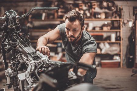 Bike is zijn leven. Zekere jonge man repareren van de motorfiets in reparatiewerkplaats