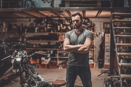 motorcycle repair shop: This is my place! Confident young man keeping arms crossed and looking at camera while standing near his motorcycle in garage or repair shop