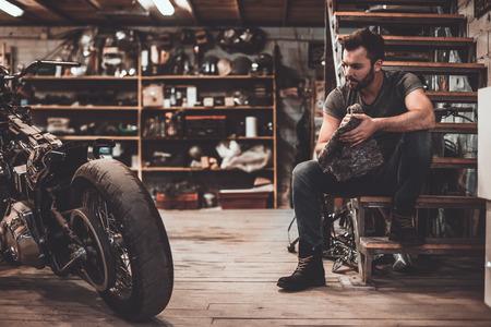 자신감이있는 정비공. 누더기를 들고 오토바이를 근처에 앉아있는 동안 수리 샵에서 확신 확신 젊은 남자