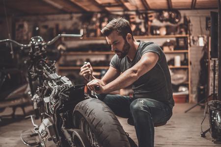 このバイクは完璧になります。自信を持って若い男の修理店で修理のオートバイ