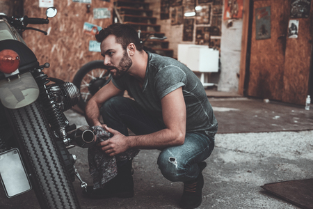 crouching: What seems to be a problem? Confident young man holding rag and looking at motorcycle while crouching near it with garage in the background Stock Photo