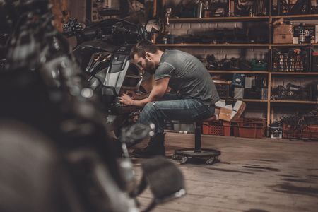 motorcycle repair shop: Spending time with bikes. Confident young man repairing motorcycle in repair shop