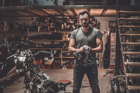 motorcycle repair shop: Confident mechanic. Confident young man holding rag and looking at camera while standing near motorcycle in repair shop