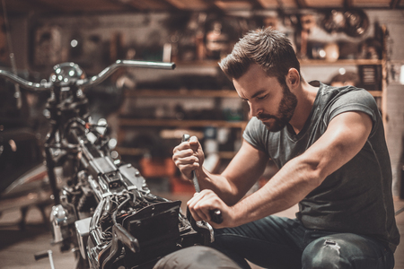 motorcycle repair shop: This bike should be perfect. Confident young man repairing motorcycle in repair shop