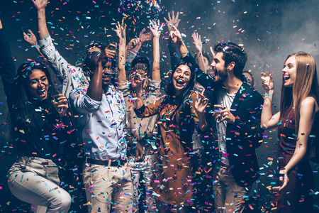 S'amuser ensemble Groupe de beaux jeunes jetant des confettis colorés et l'air heureux Banque d'images - 64179705