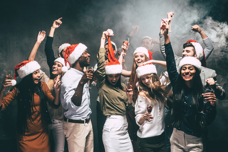 new year party: New Year party with friends. Group of beautiful young people in Santa hats dancing and looking happy Stock Photo