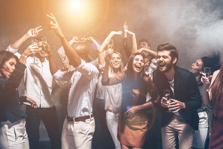 Il divertimento è tutto di cui hanno bisogno stasera. Gruppo di belle giovani a ballare insieme e cercando felice Archivio Fotografico - 64179710
