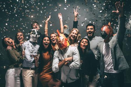 Dit is mijn jaar! Groep jonge mensen in dierlijke maskers gooien van confetti en zoekt graag