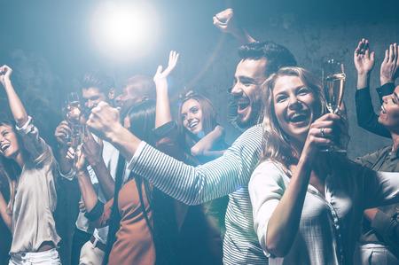 밤새 춤. 젊은 사람들이 샴페인 피리와 함께 춤과 행복을 찾고 그룹