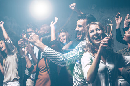 Dansen de hele nacht lang. Groep van mooie jonge mensen aan het dansen met champagne fluiten en op zoek gelukkig Stockfoto