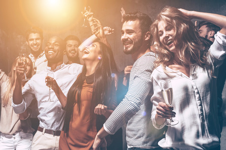 gente che balla: Amano ballare. Gruppo di belle giovani danzanti con champagne flauti e guardando felice