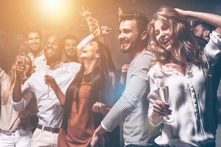 gente bailando: Les encanta bailar. Grupo de jóvenes hermosas que bailan con copas de champán y mirando feliz Foto de archivo
