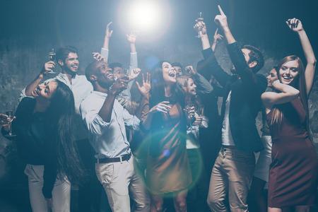 Doe je handen omhoog in de lucht! Groep van mooie jonge mensen dansen en op zoek gelukkig