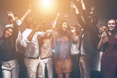 Genieten feestje met vrienden. Groep van mooie jonge mensen dansen en op zoek gelukkig Stockfoto