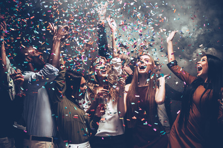 unleashed: Unleashed fun. Group of beautiful young people throwing colorful confetti while dancing and looking happy