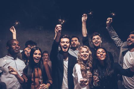 Fête avec des amis. Groupe de joyeux jeunes gens portant des cierges magiques et flûtes à champagne