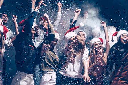 크리스마스 재미. 다채로운 색종이 조각을 던지고 행복하게 산타 모자에있는 아름 다운 젊은 사람들의 그룹