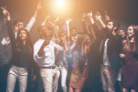 Todo lo que necesitamos es divertido! Grupo de jóvenes hermosas bailando juntos y que parece feliz