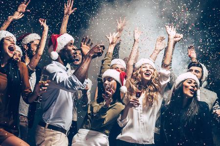 彼らはクリスマスが大好きです。サンタ帽子カラフルな紙吹雪を投げると幸せそうに見えて、美しい若者のグループ