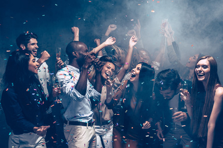Carefree fun. Group of beautiful young people throwing colorful confetti and looking happy Фото со стока