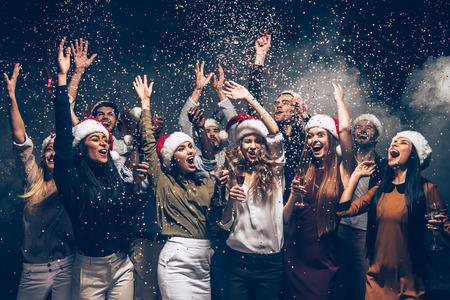 Vieren Nieuwjaar samen. Groep van mooie jonge mensen in Santa hoeden gooien kleurrijke confetti en zoekt graag