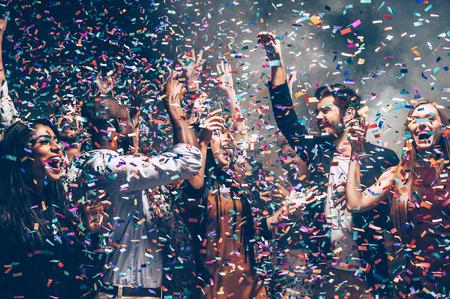 gente che balla: divertimento Confetti. Gruppo di belle giovani persone che lanciano coriandoli colorati mentre balla e cercando felice