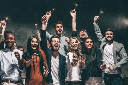 Vieren met plezier. Groep van vrolijke jonge mensen die sterretjes en champagne fluiten