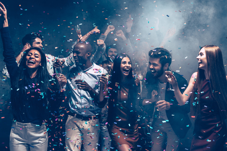 Enjoying great party together. Group of beautiful young people throwing colorful confetti and looking happy photo