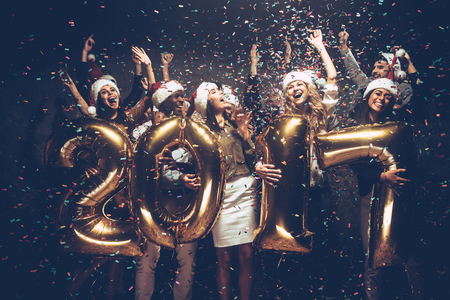 New 2017 Year is coming! Group of cheerful young people in Santa hats carrying gold colored numbers and throwing confetti photo