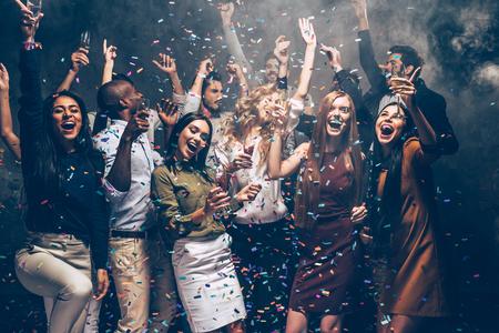 gente bailando: diversión del partido. Grupo de jóvenes hermosas que lanzan confeti de colores y mirando feliz