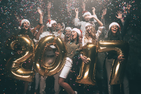 Happy New Year to you! Group of cheerful young people in Santa hats carrying gold colored numbers and throwing confetti photo