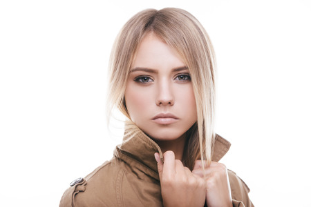 Autumn fashion. Attractive young woman in coat adjusting her collar and looking at camera while standing against white background Stock Photo