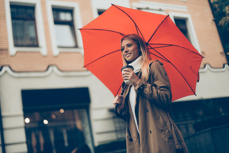 street life: City life. Low angle view of attractive young smiling woman carrying umbrella and coffee cup while walking along the street