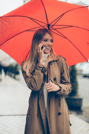 rain wet: Nice to hear from you! Attractive young smiling woman carrying umbrella and talking on the mobile phone while standing on the street Stock Photo